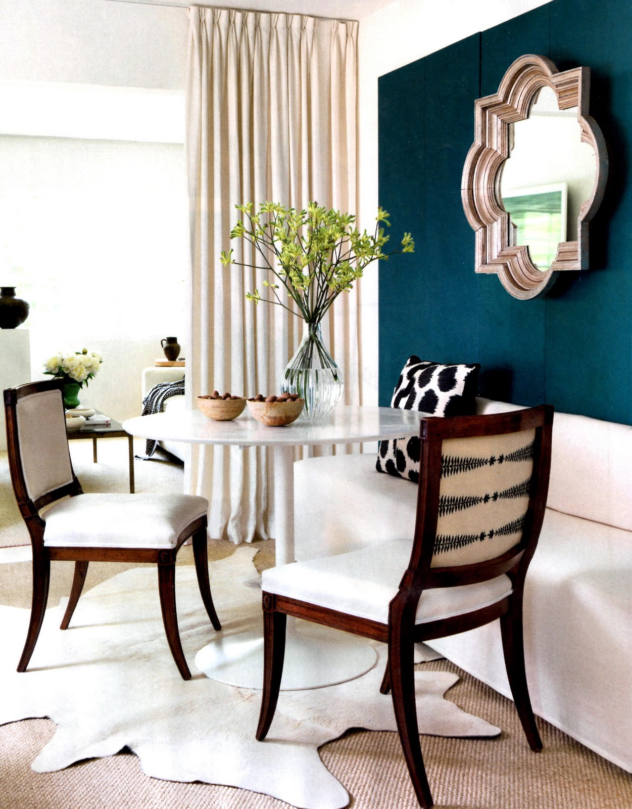 lindsey bond turquoise wall with a quatrefoil mirror and tulip table